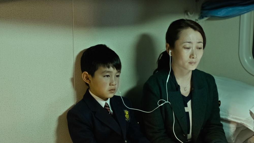 Rare moment de partage entre une mère et son fils : écouter de la musique ensemble.
